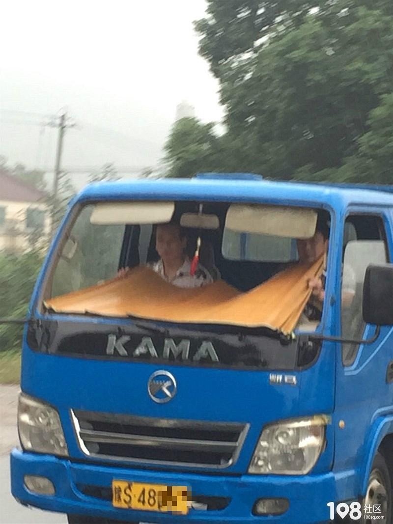 酸爽!下雨天开敞篷车,两男子边开车边拿着凉席…