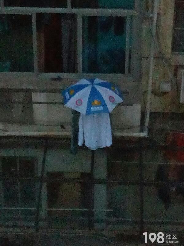 头次见!城东一村某住户晾晒有个性:下雨就给衣服撑把伞
