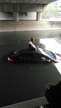把车当船开?四环桥下一车开进河里,女司机淡定坐在车顶