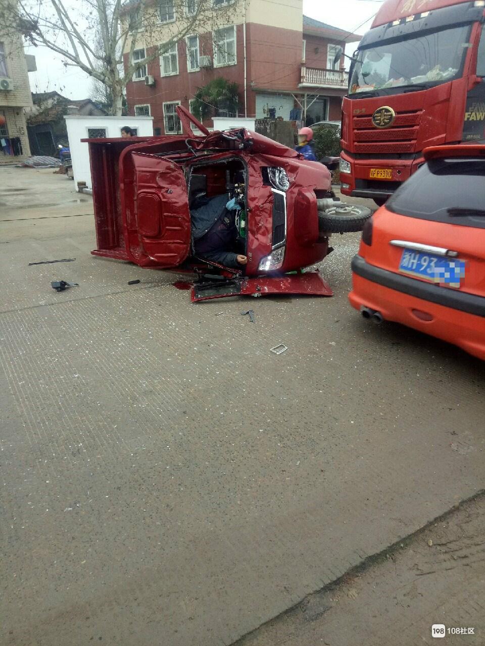 半挂车与三轮车相撞,车头严重变形,驾驶员卡在里面
