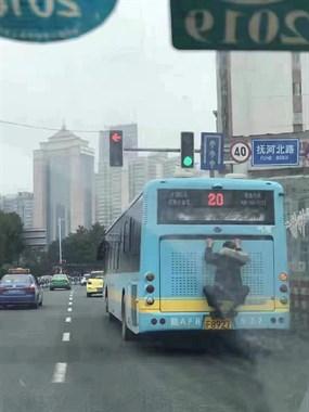 惊呆!江西男子连扒2辆公交车 青蛙一样贴车屁股上