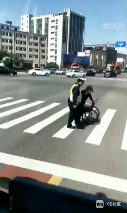 暖心!浦西红绿灯看到交警 耐心地扶残疾人过马路