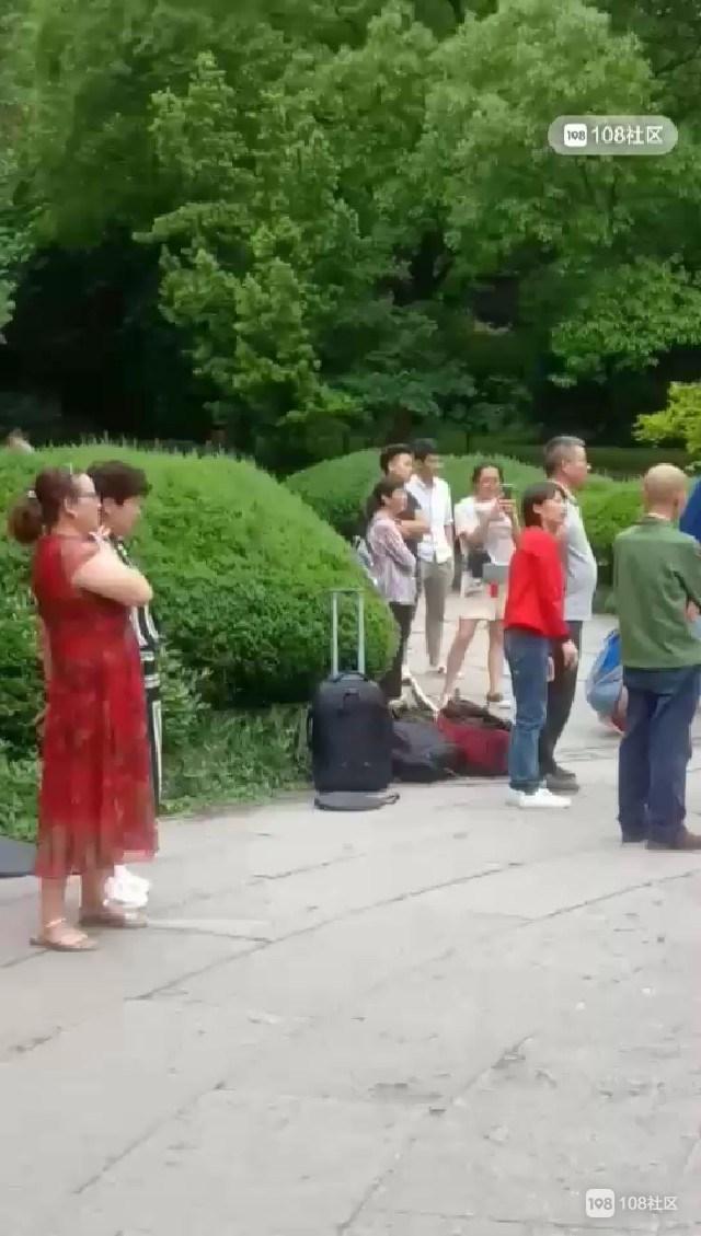 大佛寺一帅和尚在喷泉边舞枪弄棒,身边还围了一群人