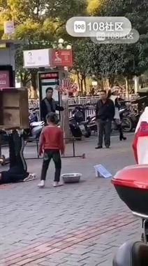 广场附近2小孩辍学表演杂技讨生活 旁边还有大人看着