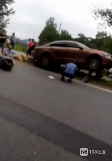 江山街头一轿车骑上隔离带,电瓶车摔倒在一旁