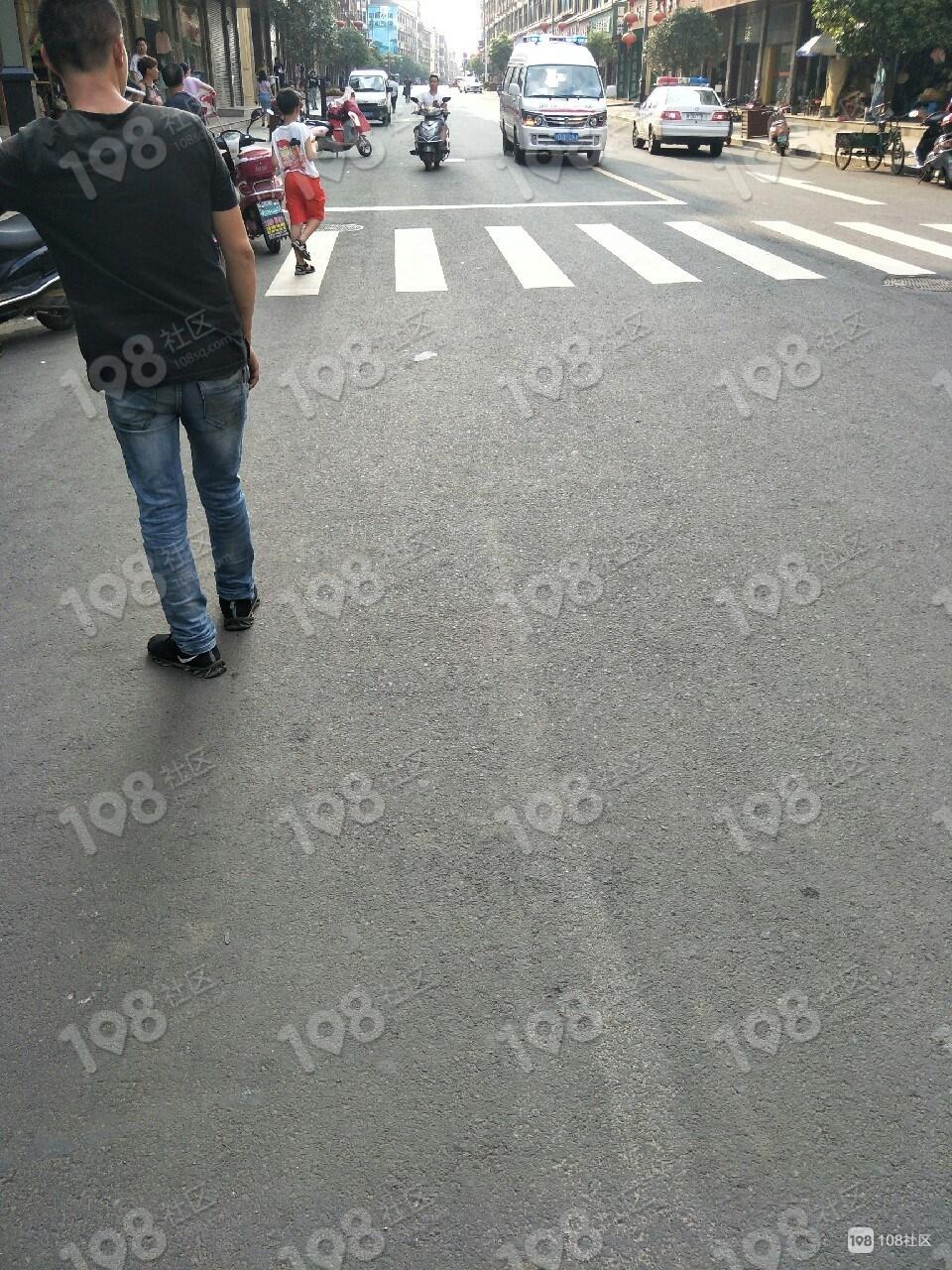大市聚一群人聚在这里,围着一妇女!120车停在旁边